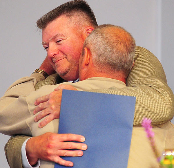 Hagerstown Police Detective Casey Yonkers, facing camera, gets a hug from David Maphis on Sunday at the 23rd annual Maryland Statewide Memorial Service for Crime Victims and Their Families at Hagerstown Seventh-day Adventist Church. The Maphis family thanked Yonkers and retired detective Steve Hoover for their investigation into the slaying of their daughter, Carol Brown.