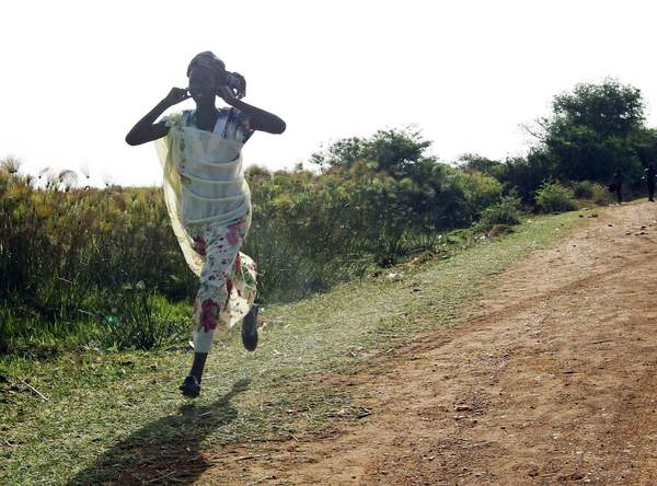 A woman runs along a road during an air strike by the Sudanese air force in Rubkona near Bentiu April 23, 2012. Sudanese warplanes carried out air strikes on South Sudan on Monday.