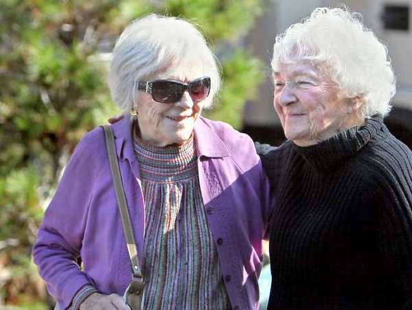 Viola Smith, left, is greeted by her cousin Marie Kolasinski, 90, as she arrives to celebrate her 99th birthday at Piecemakers Country Store in Costa Mesa on Nov. 25. Kolasinski died Monday.