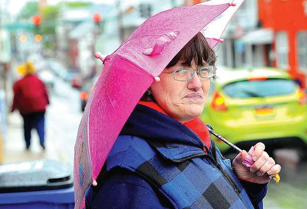 Chris Cassatt stands in the rain Monday on South Locust Street in Hagerstown afternoon trying to stay dry under her small pink umbrella.