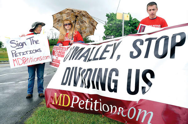 MDPetitions.com supporters from left, Anita Bussard, Nancy Allen and Philip Litton hold signs Monday at the park-and-ride near the Motor Vehicle Administration off Md. 65 south of Hagerstown while waiting for Maryland Gov. Martin O'Malley to pass.