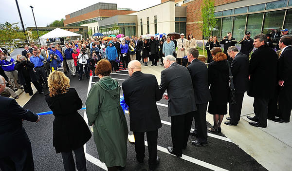 Officials and dignitaries line up to cut a ceremonial ribbon Monday at the new War Memorial Hospital in Berkeley Springs, W.Va.