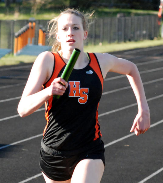 Kaitlyn Alessi of Harbor Springs takes the baton during her leg of the 3200-meter relay Monday at Reynolds Field. Alessi, along with Abby Detmar, Kyra LaRue and Taylor Sydow, won the race in 10 minutes, 54.51 seconds.