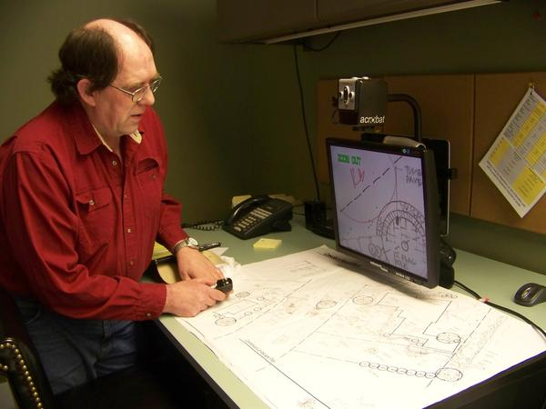 David Penfold of Vidosh Landscaping North in Petoskey, works on a garden plan with the use of a special monitor, which allows him to read the plan despite being legally blind.