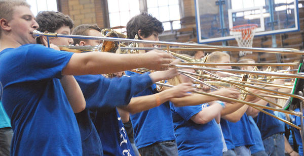 Members of the Petoskey High School jazz band trombone section extend to sixth position as they demonstrate the uniqueness of the instrument for their young elementary school audience, Friday, at the Petoskey Central Elementary School.