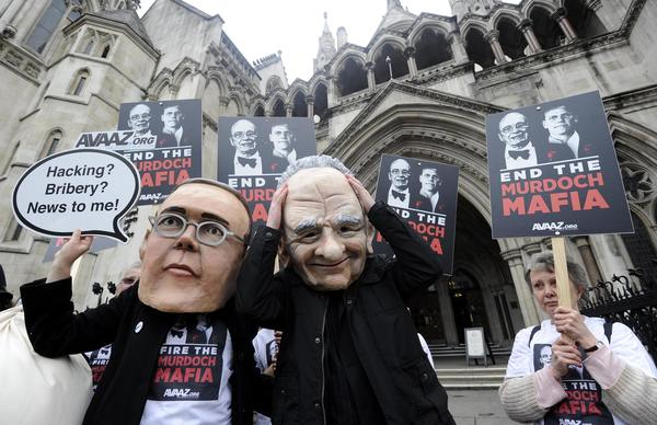 Demonstrators dressed as James (L) and Rupert Murdoch protest outside the High Court in London April 24, 2012. James Murdoch gave evidence on Tuesday to the Leveson Inquiry into the culture, practices and ethics of the media at the High Court in London.