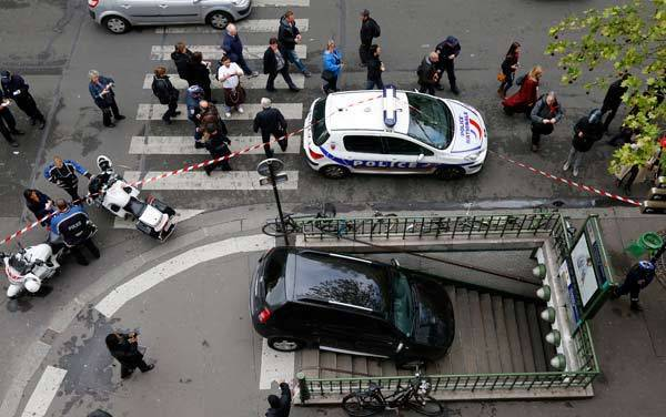 French police gather at the entrance to the Chaussee d'Antin La Fayette Metro (subway) station in Paris after a car accidentally drove into it.