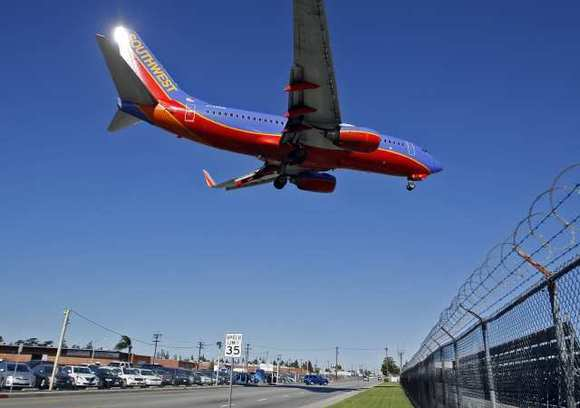 An airplane lands over W. Empire Avenue at the Bob Hope Airport in Burbank on Tuesday, April 25, 2011.