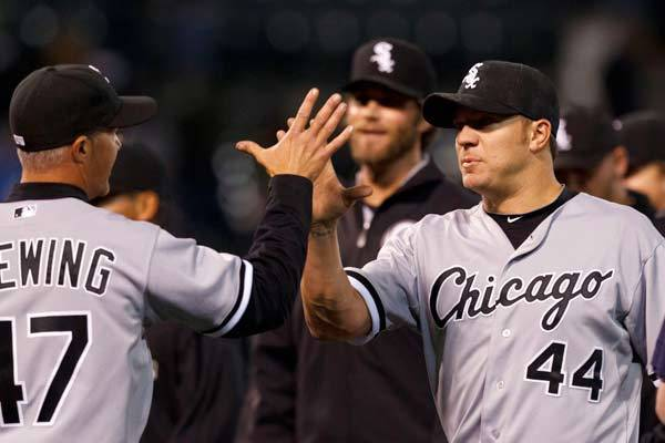 Chicago White Sox starting pitcher Jake Peavy (44) is congratulated by third base coach Joe McEwing (left) after the game against the Oakland Athletics at O.co Coliseum. Chicago defeated Oakland 4-0.