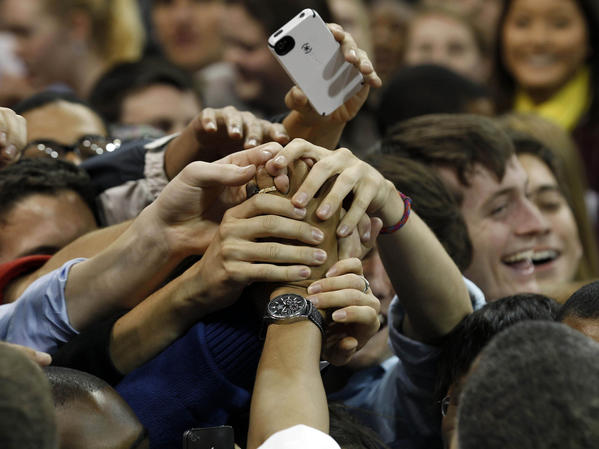 U.S. President Barack Obama's hand is grabbed by students after he spoke about the rising costs of student loans while in Carmichael Arena at the University of North Carolina at Chapel Hill.