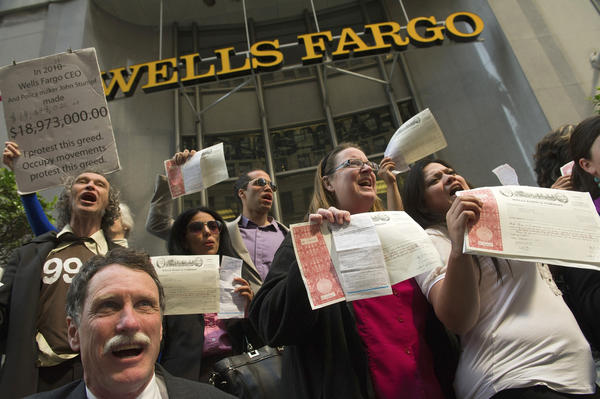 Wells Fargo & Co. shareholders hold up their share certificates and the citations they received for being arrested as they joined members of Occupy San Francisco, an off-shoot of the Occupy Wall Street movement, as they protest during a Wells Fargo & Co. annual investor's meeting in San Francisco, California. Wells Fargo & Co. shareholders needed police help to enter today's annual meeting in San Francisco as about 500 people gathered to protest the bank's lending and foreclosures.