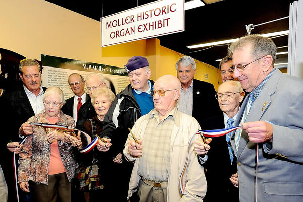 Cutting the ribbon on the new Moller Organ Co. exhibit at Discovery Station in Hagerstown are, from left, Mary Ward, Edwin Benchoff, Daisy Wolfensburger, Ellis Duffey, Jack Myers, and Joe Penner. Holding the ribbon at right is Allen Swope.