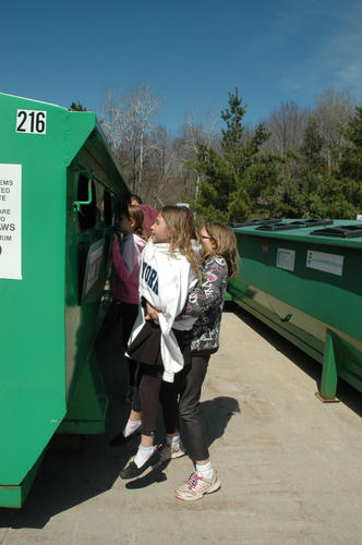 Lindsey Pop, 10, hoists Lilymarie Johnson, 9, up for a look in the recycling bins at the Emmet County Recycling Center in Harbor Springs. The Charlevoix Elementary School fourth-graders took a tour of the facility on Tuesday to learn how recyclables are processed.