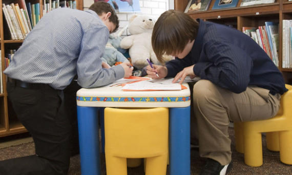 Teenagers use a play table as a work surface to fill summer job applications at a teen job fair in Nebraska. A new report suggests that teens will have an easier time finding jobs this summer.