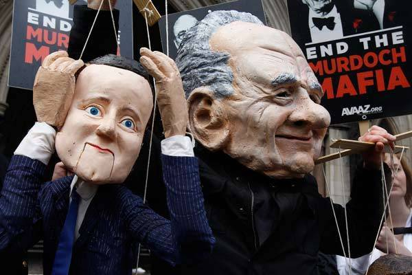 A demonstrator dressed as Rupert Murdoch protests outside the High Court in central London. Murdoch rejected accusations on Wednesday that he used his media empire to play puppet master to a succession of British prime ministers, electrifying a media inquiry that has shaken the government and unnerved much of the establishment.