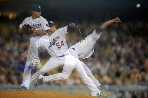 Multiple exposure of Los Angeles Dodgers reliever Javy Guerra (54) in the ninth inning against the Atlanta Braves at Dodger Stadium. The Braves defeated the Dodgers 4-3.