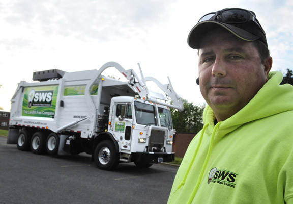 Nick DiCiacco of Perkiomenville, a front-load driver for SWS, stands with his company's compressed natural gas garbage truck on the campus of Muhlenberg College Wednesday. As far as he knows it is the only one of its kind in Pennsylvania.
