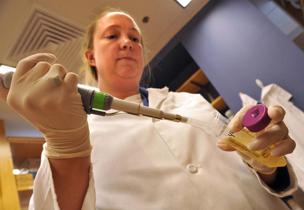 Dr. Jennifer Schwartz, research associate in the lab of Dr. Vincent Bruno, using a pipetman to extract cultures for research into how yeast causes disease, at the Institute for Genome Sciences at the University of Maryland Biopark.