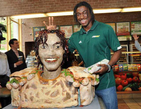Robert Griffin III poses with a statue of him made of Subway Smokehouse BBQ chicken.