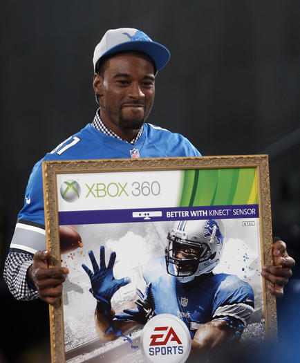 "Detroit Lions receiver Calvin Johnson holds up a poster after being named the cover athlete during the ""Madden NFL 13"" cover unveiling on the set of SportsNation at Times Square in New York."