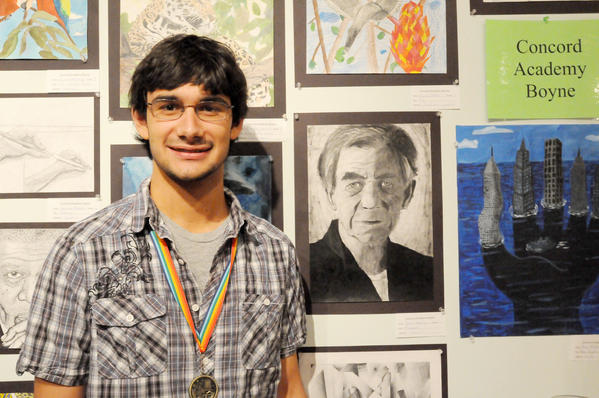 "Jordan Meicher, a junior at Concord Academy Boyne, stands next to his charcoal sketch ""Magneto,"" which won him the 2012 Youth Art Show M. Louise Herlocher Award."