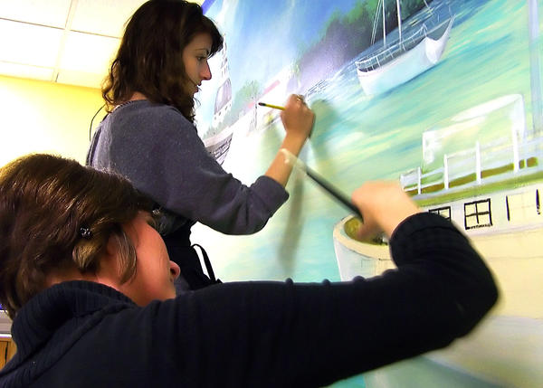 North Hagerstown High School art teacher Brandy Merchant, left, and senior Alicia Lamarche work to complete an Annapolis waterscape mural on a wall in the witness room at Washington County Courthouse.