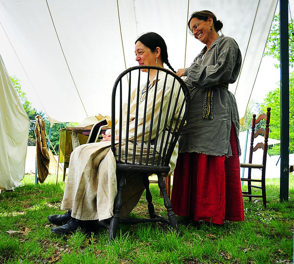 Carla Brown has her hair braided by Linda Landis Friday at Market Faire in Fort Frederick State Park. Brown, of Oxford, Pa., portrays a woman of eastern native American and colonial mix, and Landis, of Harrisonburg, Va., represents a frontiersman's wife in the 1750s. The two women are cousins.