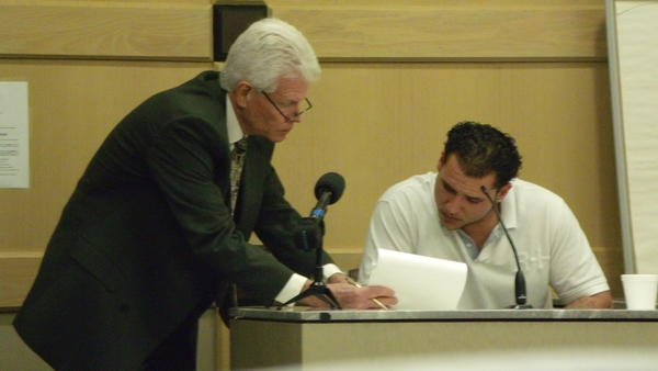 Defense lawyer Christopher Pole, left, shows witness Shawn Tundidor a transcript of a statement he made in a previous deposition. Tundidor testified Thursday against his father, Randy W. Tundidor, who is on trial for the April 2010 murder of his landlord, Joseph Morrissey.