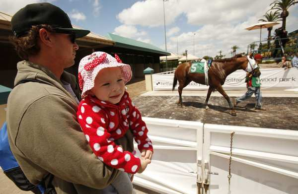 Bobby Summers of El Segundo brings his nearly 2-year-old daughter to watch the horses on opening day at Betfair Hollywood Park on Thursday.