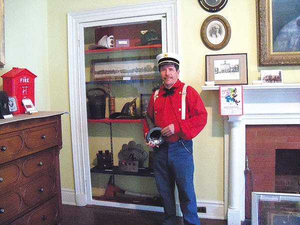 Justin Mayhue holds a ceremonial fire ground trumpet, which is part of an exhibit of historic firefighting equipment and artifacts at the Miller House, 135 W. Washington St. in Hagerstown.