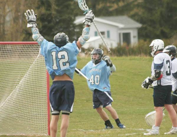 Petoskey Lacrosse Club members Connor Case (12) and Chase Ledingham (40) celebrate a goal Thursday during a 13-0 victory over Sault Ste. Marie.