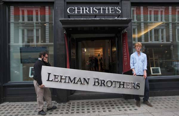 Christie's employees pose for a photograph with a Lehman Brothers sign prior to an auction of Lehman Bros.