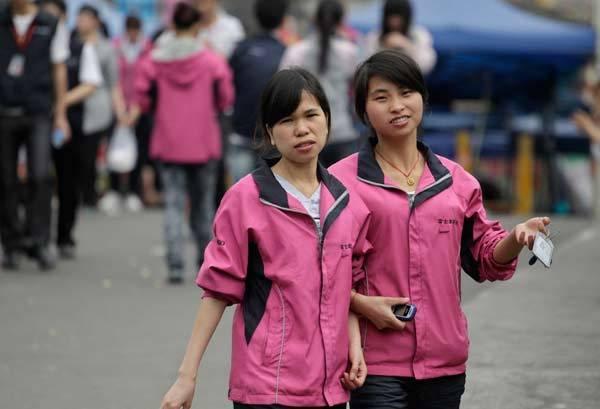 Employees in Foxconn uniforms walk near a Foxconn factory (not pictured) during lunch break in Shenzhen.