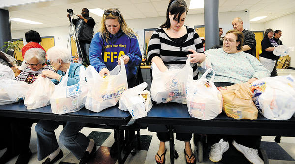 From left, Carolyn Elliott, Nancy Snyder, Kristin Friend, Rachel Lancaster and Ann Walker check bags to make sure they contain plenty of food on March 31 at Eagle School Intermediate in Martinsburg, W.Va. The women are participating in a packing day for the Bags of Love program, which provides food on weekends and during breaks from school to 500 children in 26 schools in Berkeley and Jefferson counties.