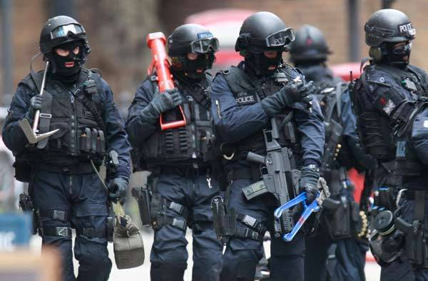Armed police officers walk in Tottenham Court Road in central London.