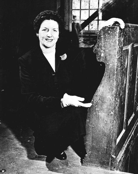 "Mary Vernon Mish, past president of the Washington County Historical Society and chairman of the Restoration Committee of the Hager House, kneels next to the newel post in the house in May of 1952, revealing ""Jacobean Paneling"" at the head of the stairs on the upper floor of the house."