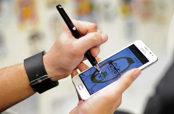 A man uses a Samsung Galaxy Note to draw a picture at the Mobile World Congress in Barcelona.