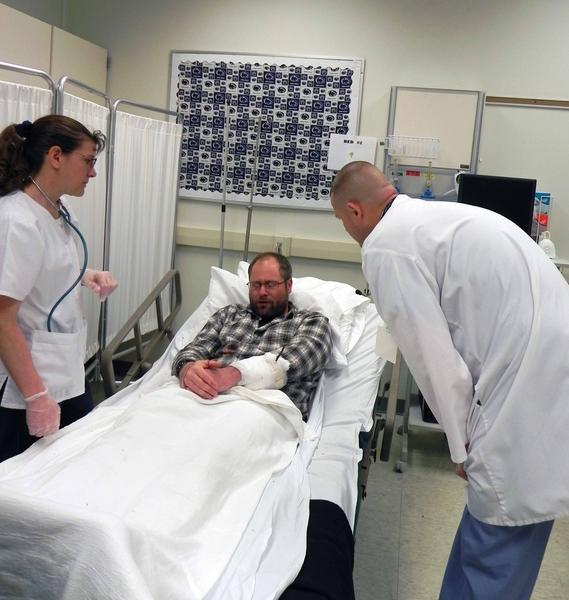 Penn State Mont Alto student nurse Dawn Dellinger and a Waynesboro Hospital physician assistant, acting as ER physician, render medical treatment for mock patient Jason Owings, forestry student, during Friday's trauma-scenario at the campus.