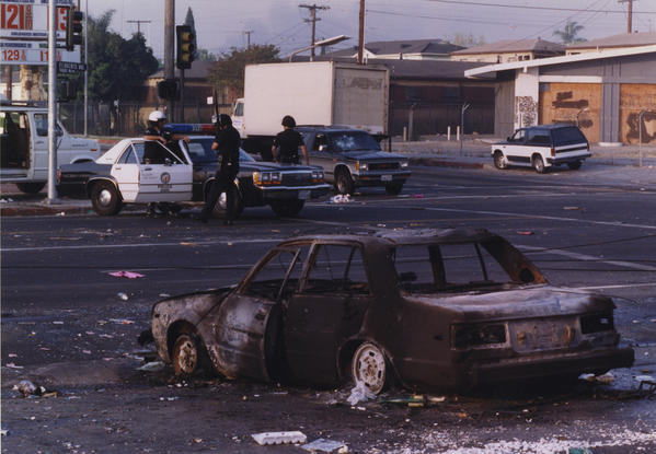 A burned-out car is seen at the intersection of Florence and Normandie on April 29, 1992.