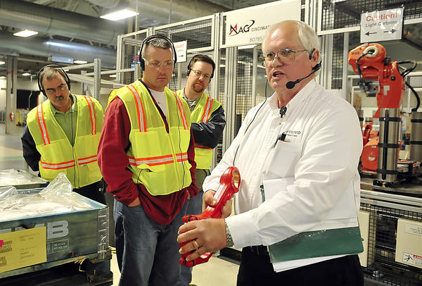 Retired engineer and Volvo Powertrain tour guide, Lamar Sease, right, guides members of Leadership Washington County Class 25 through the assembly lines of the Volvo Powertrain facility in Hagerstown, Friday.