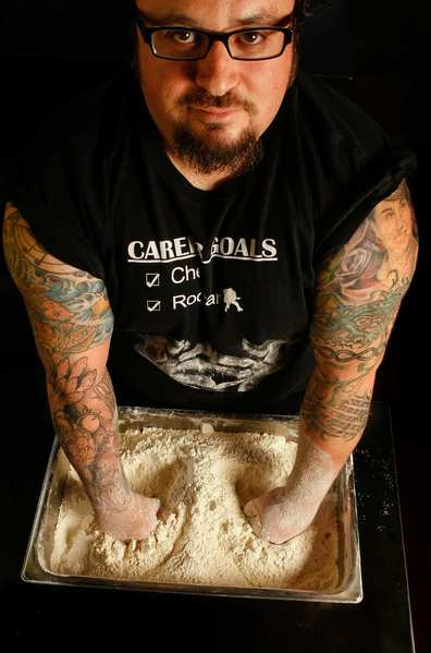 Chef Bruce Kalman of Urbano Pizza Bar displays his tattoos. The newest additions on his lower right arm are dedicated to fruit and vegetables.