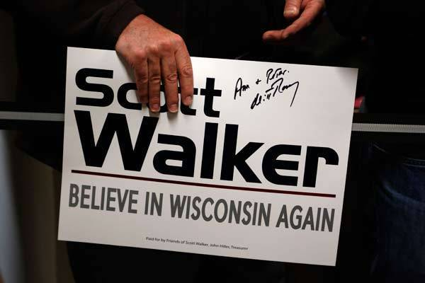 A supporter holds a sign autographed by U.S. Republican presidential candidate Mitt Romney after he attended a phone bank on behalf of Wisconsin Gov. Scott Walker in Fitchburg, Wis.