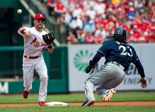 St. Louis Cardinals second baseman Skip Schumaker (55) turns a double play over Milwaukee Brewers second baseman Rickie Weeks (23) at Busch Stadium.