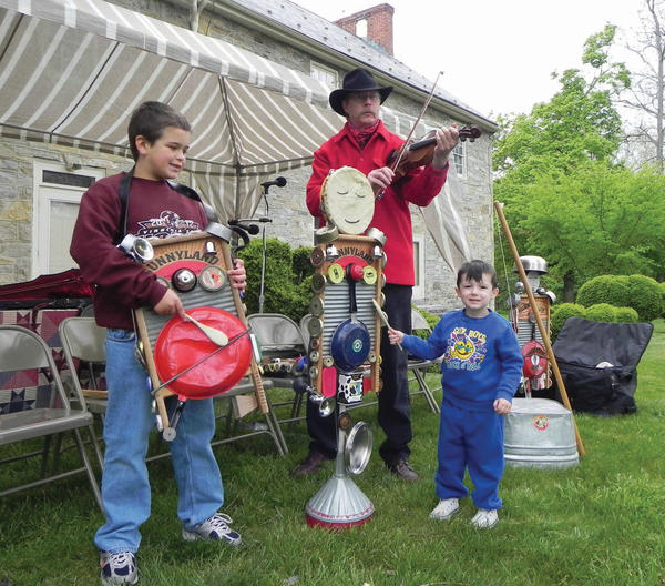 Jacob Robinson, 8, and Izayis Baumgardner, 3, play a tune with Slim Harrison of Slim Harrison's Sunnyland Band on Saturday at Renfrew Institute's Earth Celebration Day and Festival of Art in Waynesboro, Pa.
