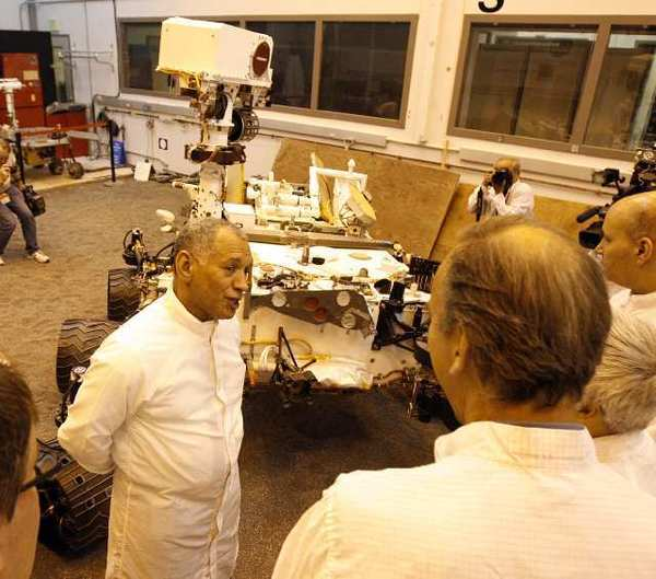 NASA Administrator Charles Bolden talks with scientist and engineers at JPL next to a duplicate of the Mars Rover Curiosity at JPL. The room is bathed in light that is similar to the light on the martian planet.
