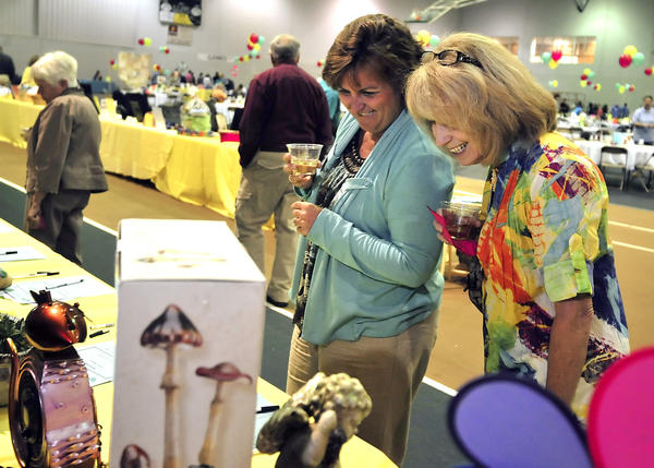 Suzie Menard of Hagerstown, left, member of the board of directors for Habitat for Humanity of Washington County and Vicki Blevins of Fairfield smile while looking at a whimsical fan shaped like a cat, one of many silent auction items at the 19th annual Habitat for Humanity Dinner and Auction at Hagerstown Community College's Athletic, Recreation and Community Center on Saturday.