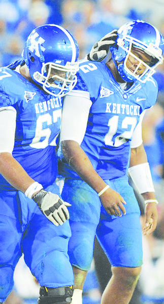 Kentucky guard Larry Warford, left, with quarterback Morgan Newton during a 2011 game, is one of only two returning starters on the Wildcats offensive line.