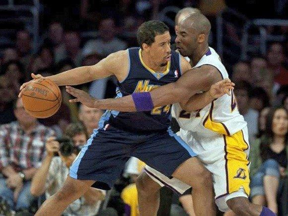Lakers guard Kobe Bryant tries to disrupt the dribble of Nuggets point guard Andre Miller in the first half Sunday afternoon at Staples Center.