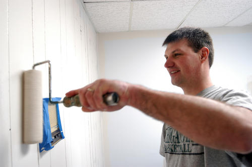 Leadership Charlevoix County participant Tom Cannon, of East Jordan, paints interior walls Saturday at the Boyne Area Free Clinic in Boyne City.