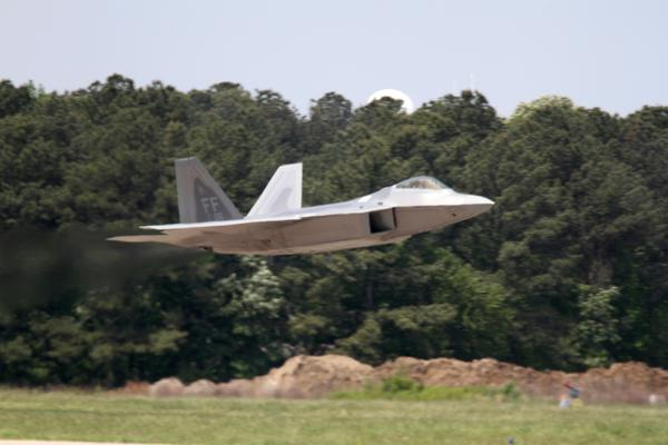 An F-22 Raptor streaks down the runway during takeoff at Langley Air Force Base.